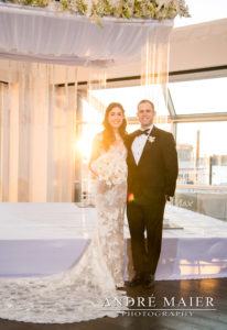 bride and groom standing at Current, sunset is in the background
