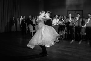 Groom holding bride while dancing in the dance floor, guests are observing in the background
