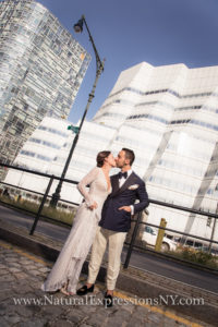 Bride and groom kissing at Pier 59 with modern building (IAC) in the background