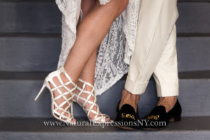 bride is showing her designer shoes from under her dress and next to her is the groom wearing white pants and blue loafers