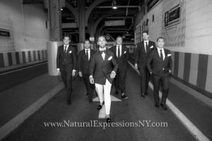 Groom and groomsmen posing at the entrance of Pier 59, black and white picture