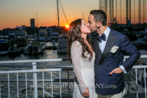Bride and groom kissing, standing in the Current Veranda, with the sunset over the marina