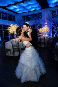 Bride and Groom kissing in the middle of the ballroom set for dinner at Current