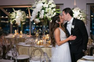 Bride and Groom kissing, tables set for dinner in the background