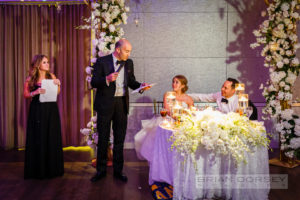 father of the bride is giving a speech to his left bride and groom are seated at their table