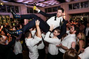 Groom being lifted by groomsmen
