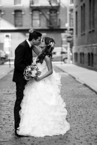 Bride and Groom in the neighborhood of Chelsea kissing while being in the middle of a cobble stone street.