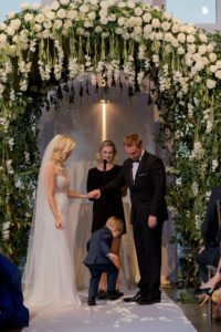 Bride, groom, minister and child under the flower arch during the ceremony at Current