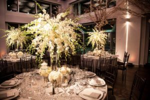 Dinner tables with white tall center pieces and amber lighting in the background