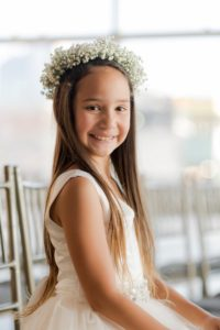 flower girl seated on a chair with a flower crown smiling for the picture