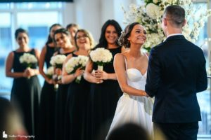 Bride standing at the ceremony, holding the groom's hands, she is smiling, and bridesmaids are behind her