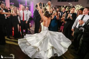 Bride showing her dress spread while dancing with groom at Current