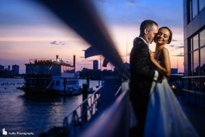 Sunset over the marina in purple and pink colors, bride and groom holding each other in the Current Veranda